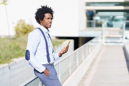 Black man with afro hairstyle using a smartphone near an office building. Imagens