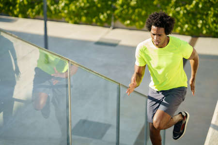 Black man running upstairs outdoors. Young male exercising.