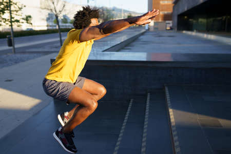 Black man doing squats with jumping on a step. Imagens