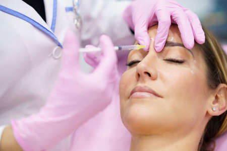 Aesthetic doctor injecting botulinum toxin into the forehead of her middle-aged patient. Imagens