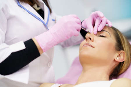 Doctor performing rhinoplasty by injection of hyaluronic acid in the nose of his patient.