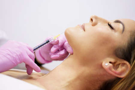 Doctor injecting hyaluronic acid into the ching of a woman as a facial rejuvenation treatment.