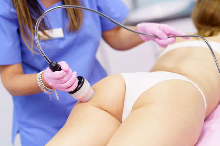 Woman receiving anti-cellulite treatment with radiofrequency machine in an aesthetic clinic. Imagens