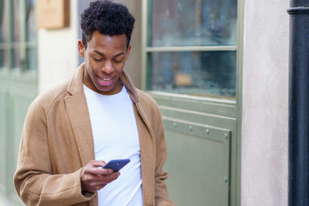 Young black man consulting his phone while walking down the street. Imagens
