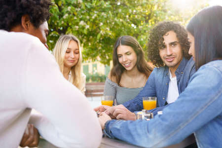 Multi-ethnic group of friends having a drink together in an outdoor bar.