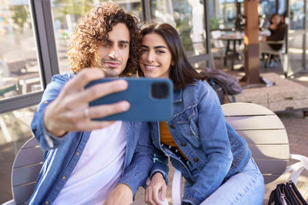 Arab couple taking selfie pictures with their smartphone, sitting on the terrace of a bar. Imagens