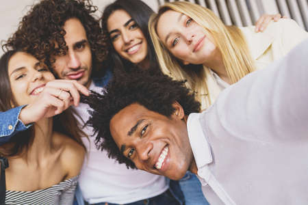 Multi-ethnic group of friends taking a selfie together while having fun outdoors. Imagens