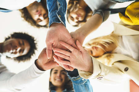 Hands of a multi-ethnic group of friends joined together as a sign of support and teamwork.