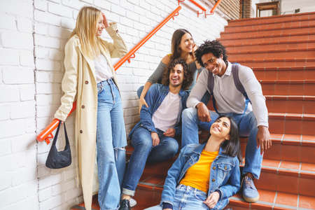 Group of friends with ethnic variety, sitting on some street steps having fun together.