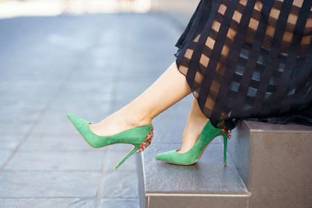 Attractive woman wearing skirt and green high heels outdoors.