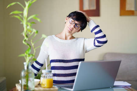 Middle-aged woman teleworking taking a stretch break.