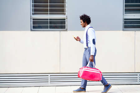 Black man with afro hairstyle carrying a sports bag and smartphone outdoors.