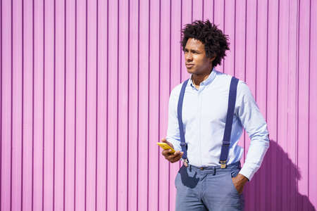 Black man with afro hairstyle carrying a sports bag and smartphone in yellow background.