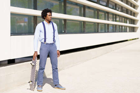 Black male worker standing next to an office building with a skateboard.