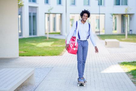 Black businessman riding skateboard near office building. Imagens