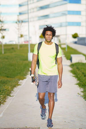 Black man going for a workout in sportswear and a skateboard.