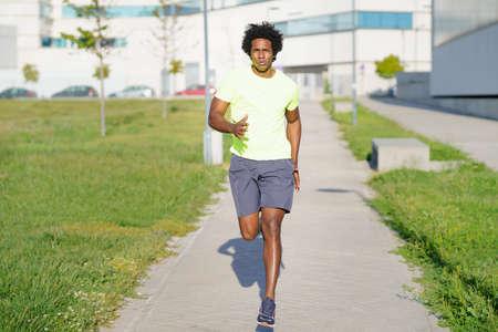 Black athletic man running in an urban park.