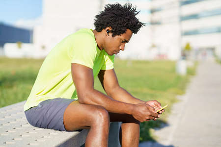 Black man consulting his smartphone with some exercise app while resting from his workout.