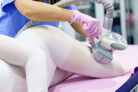 Woman in special white suit having a anti cellulite massage with spa apparatus