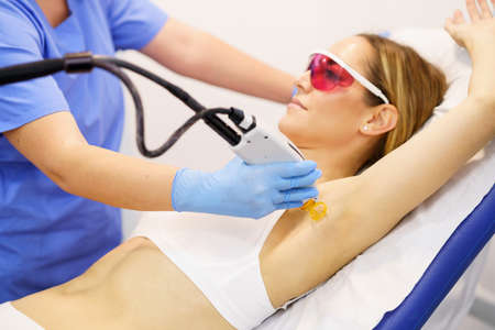 Woman receiving underarm laser hair removal at a beauty center. Laser depilation treatment in an aesthetic clinic.