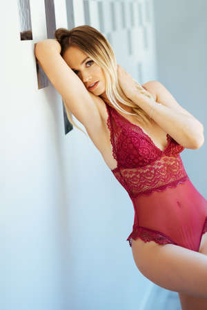 Caucasian girl in red lingerie posing in the hallway of her home