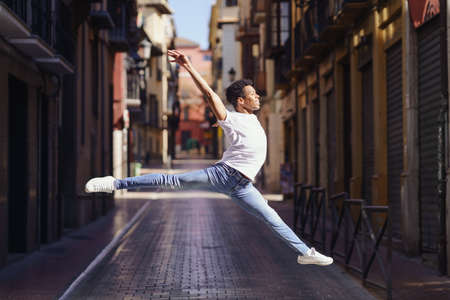 Young black man doing an acrobatic jump in the middle of the street.