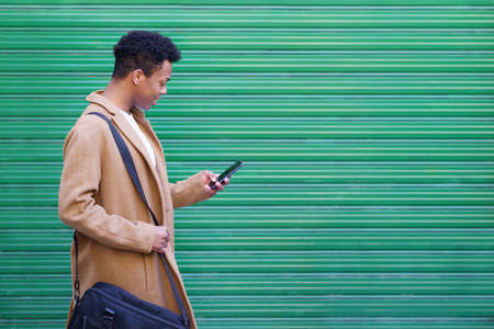 Black young man using a smartphone near a urban wall. Imagens
