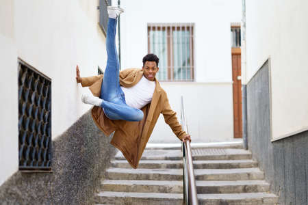 Young black man jumping for joy over a handrail in the street.
