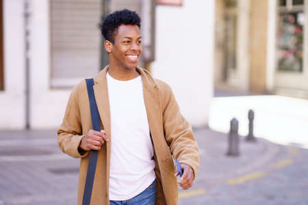 Happy black man walking down the street carrying a briefcase and a smartphone in his hand.
