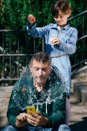 Girl blowing up a water-filled balloon over her fathers head Imagens