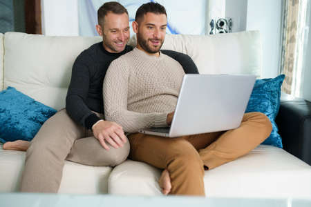 Gay couple consulting their travel plans together with a laptop.