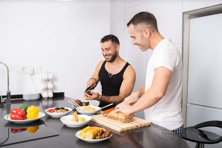 Gay couple cooking healthy vegan food together at home.