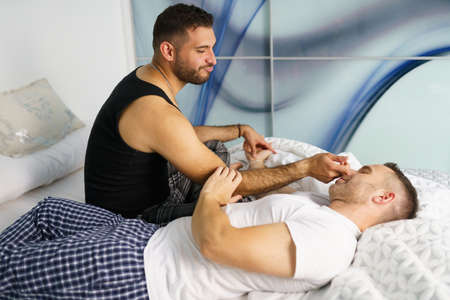Gay couple talking in a romantic moment on their bed.
