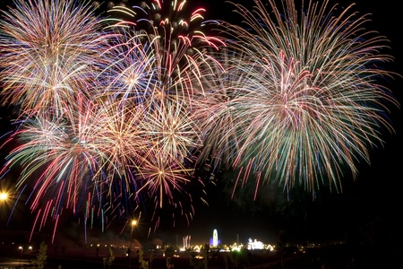 Panoramic view of fireworks over a fair in the night Foto de archivo