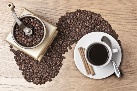 Cup and mill with coffee beans over a wooden background photo
