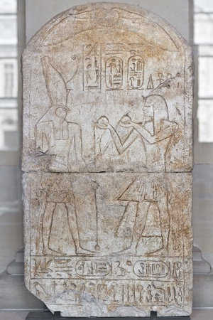 Egyptian hieroglyph carved in the stone. Ramses III offering wine glasses to the God Horus.