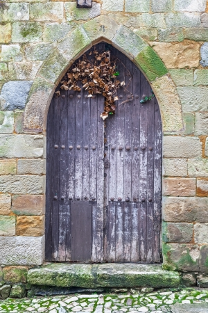 Ancient wooden door with stone frame photo