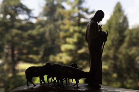 Escultura de Jesucristo con rebaño de corderos en la luz de fondo Foto de archivo