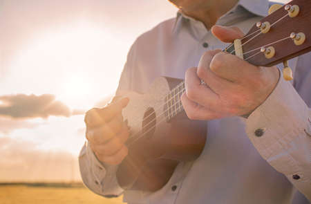 man playing ukulele in the countryside at sunset 写真素材