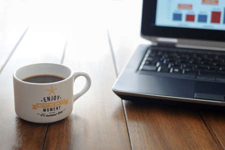 coffee cup with message enjoy every moment it is summer time on a wooden table and a computer out of focus in the background