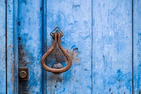 detail of an antique door knocker on a blue wooden door with a lock, horizontal