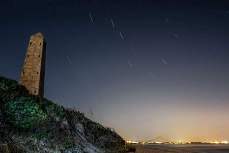 night image of a beach with a stone monolith, lights and city in the background and a line of a star forming a circumpolar, in Playa de Muro, Palma de Mallorca, Spain