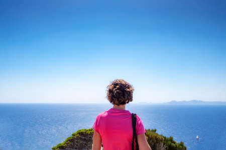 young woman on her back in a pink T-shirt contemplates the horizon from a cliff with the sea in the background, panorama