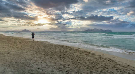 man running on a lonely beach at sunset on a cloudy day, Playa de Muro, Palma de Mallorca, Balearic Islands, Spain, panoramic format