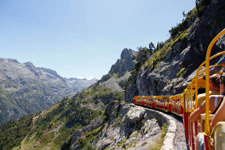 tourist train full of people running through a mountain gorge in the Pyrenees, Artouste France, rear view Foto de archivo