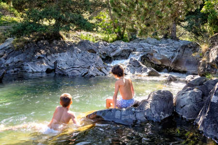 two boys on their backs enjoying a swim in a clear mountain river in a rocky, sunlit pool with rocks all around Stock fotó