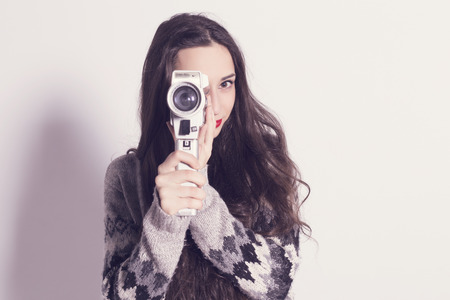 camera film: Beautiful modern girl recording with a very old and dirty Super 8mm camera