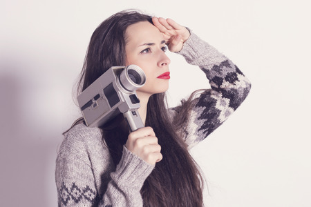 very dirty: Beautiful modern girl with a very old and dirty Super 8mm camera saluting to the sky Stock Photo