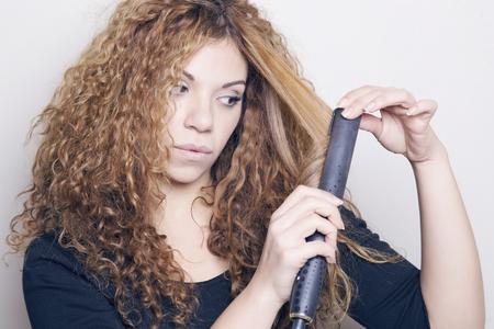 Femme avec un lisseur de cheveux, planche à ses cheveux. Banque d'images