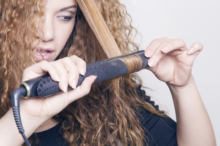 Woman with a hair straightener, ironing her hair.